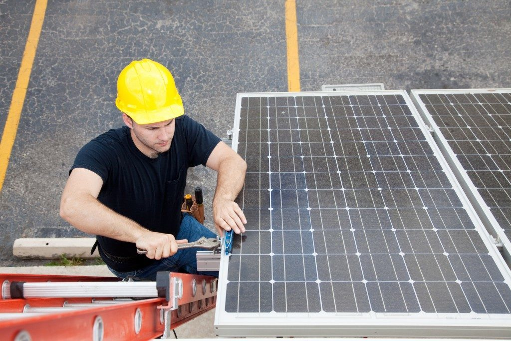 Worker repairing a solar panel